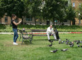 Man is feeding pigeons elder sitting on the bench in the park at king tomislav square and the young girl taking a picture zagreb Royalty Free Stock Image