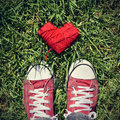 Man feet and heart-shaped coil of red cord on the grass, vignett Royalty Free Stock Photo