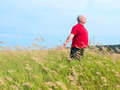 Man in field with breeze an older a of grass enjoying the gently blowing Stock Images