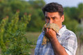 Man in the field suffers from allergies blowing his nose and suffering hay fever Stock Photo