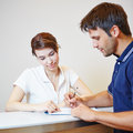 Man filling out patient form at doctors office with the help of a assistant Royalty Free Stock Images