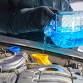 Man filling a windshield washer tank of a car by antifreeze Royalty Free Stock Photo