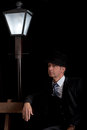 Man film noir man lamppost bench or private detective with hat and suit sitting on a wooden beside a street lantern on a black Stock Photography