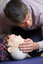 Man In First Aid Class Checking Airway On CPR Dummy Royalty Free Stock Photo