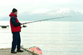 Man fishing in fiord side view of with snow capped mountain background norway Stock Images