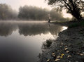 Man fishing fisherman sitting and by the lake in the fog Stock Images