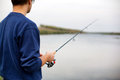 Man fishing holding rod freshwater lake Stock Image
