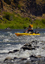 Man fishing while paddling a kayak near rapids in river in the wilderness Royalty Free Stock Photo