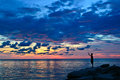 A man fishing during sunset silhouette of with beautiful and colorful decorated sky as background Stock Photo