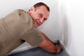 Man fitting carpet into a corner Royalty Free Stock Images