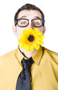 Man with flower in mouth nerdy young yellow white background Royalty Free Stock Images