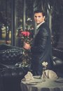 Man with flowers waiting his lady in restaurant handsome bunch of red roses Stock Photos