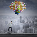 Man flying with balloons young asian over the cityscape Stock Photography