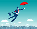 Man flying in the sky above the city with red umbrella in his ha