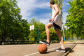 Man with foot on basketball looking towards basket low angle view of young athletic standing side lines of court top of ball Royalty Free Stock Photography