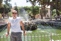 Man by fountain on sunny day Stock Images