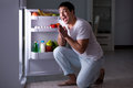 The man at the fridge eating at night Royalty Free Stock Photo