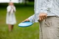 Man with frisbee midsection of men in casual clothing ready to throw women in background Royalty Free Stock Images