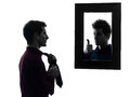 Man in front of his mirror dressing up silhouette men shadow white background Royalty Free Stock Photo