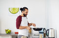 Man with frying pan cooking food at home kitchen Royalty Free Stock Photo