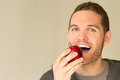 Man with funny face looking at an apple open mouth and beard Royalty Free Stock Photos
