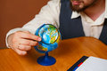 Man geography teacher looking at globe through a magnifying glass back to school Stock Image