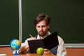Man geography teacher makes notes in a notebook back to school Royalty Free Stock Image