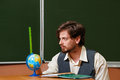 Man geography teacher measures the globe back to school Stock Photos