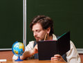 Man geography teacher stares at the globe holding a notebook back to school Stock Photography