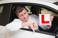 Man gesturing thumbs down holding a learner driver sign Royalty Free Stock Photo