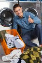 Man gesturing thumbs up at laundry portrait of young with dirty clothes on floor Stock Photo