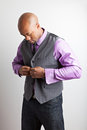 Man getting dressed in his thirties in business casual style buttons his vest Royalty Free Stock Photo