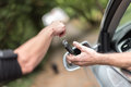 Man getting his car keys woman handing another person automobile Royalty Free Stock Image