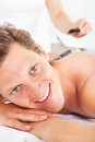 Man getting hot stone massage young relaxing in a spa lastone therapy Royalty Free Stock Image