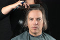 Man getting long hair combed in preparation for cut close up of a serious men looking to camera while his is having it off a Royalty Free Stock Photography