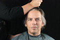 Man getting long hair shaved off for cancer fundraiser close up of a serious men looking to camera while his is a Stock Image