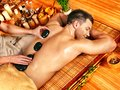 Man getting stone therapy massage in bamboo spa Royalty Free Stock Images