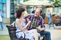 Man and girl with flower at street bench on a date Stock Photos