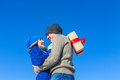 Man and the girl hug on a background of colored houses with gift Royalty Free Stock Photo