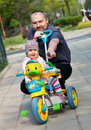 Man and girl with tricycle Royalty Free Stock Images