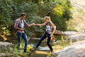 Man girlfriend crossing stream young men helping at mountain valley Stock Photography