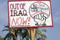 A man gives the peace sign and holds a sign saying out of iraq now at an anti iraq war protest march in santa barbara california Stock Photo