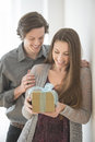 Man giving birthday present to woman at home smiling young men women Royalty Free Stock Images