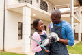 Man giving flower wife african men to his in their front yard Royalty Free Stock Images