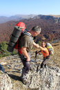 Man giving helping hand to friend to climb mountain rock cliff. Royalty Free Stock Photo