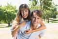 Man giving his pretty girlfriend a piggy back in the park smiling at camera on sunny day Royalty Free Stock Photo