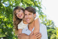 Man giving his pretty girlfriend a piggy back in the park smiling on sunny day Royalty Free Stock Photo