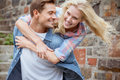 Man giving his pretty girlfriend a piggy back on sunny day in the city Stock Images