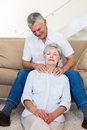 Man giving his relaxed senior wife a shoulder rub at home in living room Stock Photos