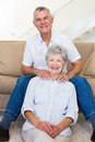 Man giving his relaxed senior wife a shoulder rub smiling at camera home in living room Stock Photos